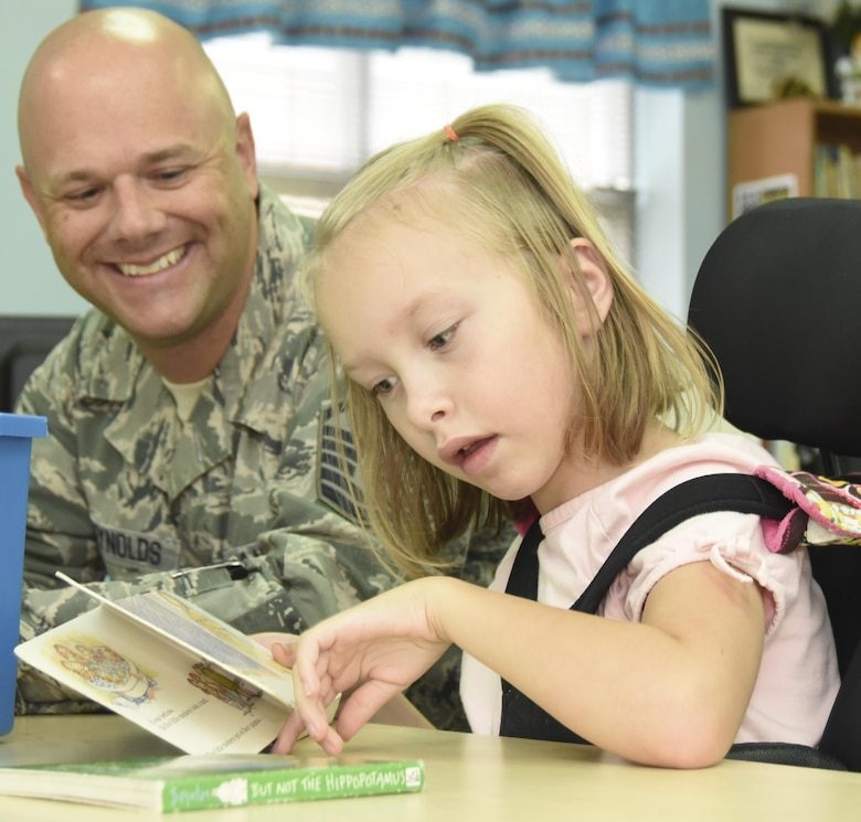 Master Sgt. Nate McReynolds, 301st Medical Squadron surgical technician, reads to a student and neighbor Aug. 23, 2017, at Lone Star Elementary School in Keller, Texas. Eight Reserve medical Airmen visited the school to connect and read to students as part their unit's community outreach program. (U.S. Air Force photo by Ms. Julie Briden-Garcia)