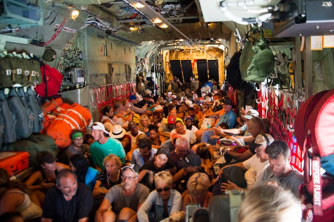 Evacuees sit on the floor of a HC-130 Hercules aircraft.