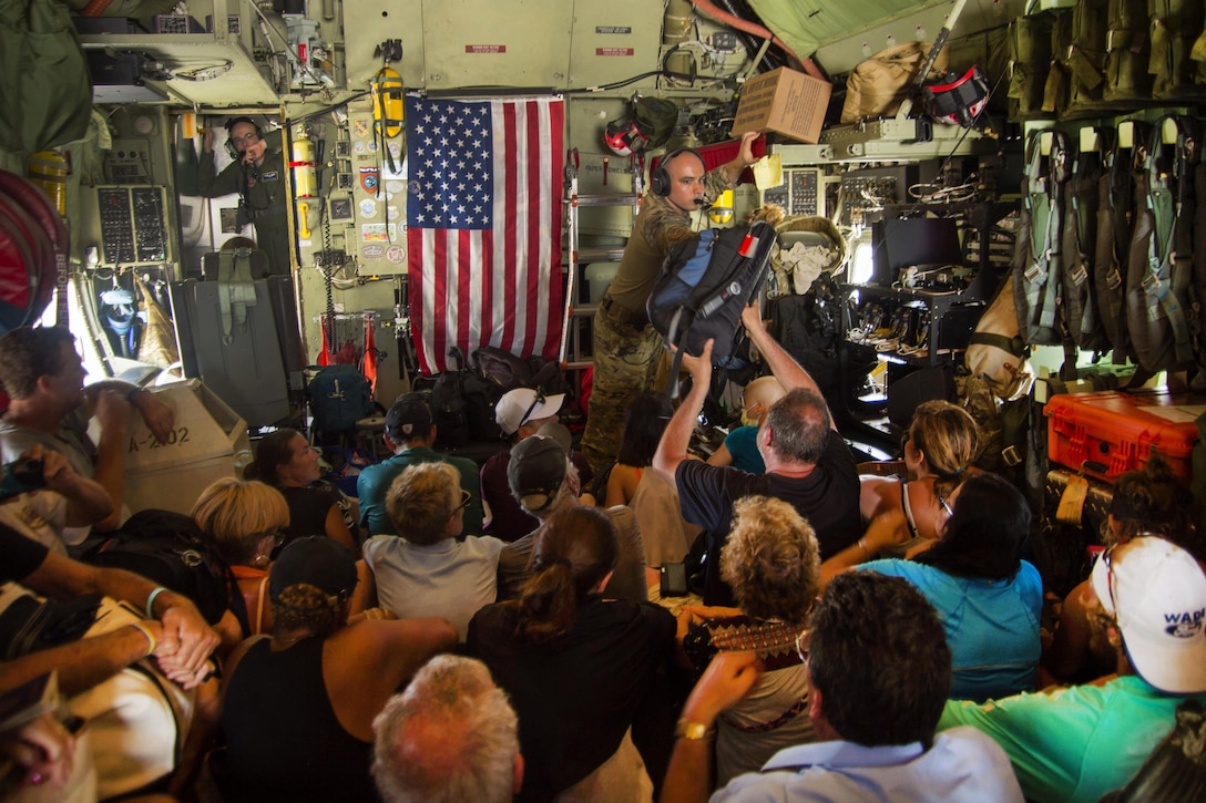 An airman hands a person a bag while inside an aircraft.
