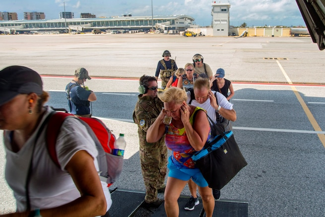 American evacuees board a HC-130 Hercules aircraft at the Princess Juliana International Airport on St. Maarten before taking off