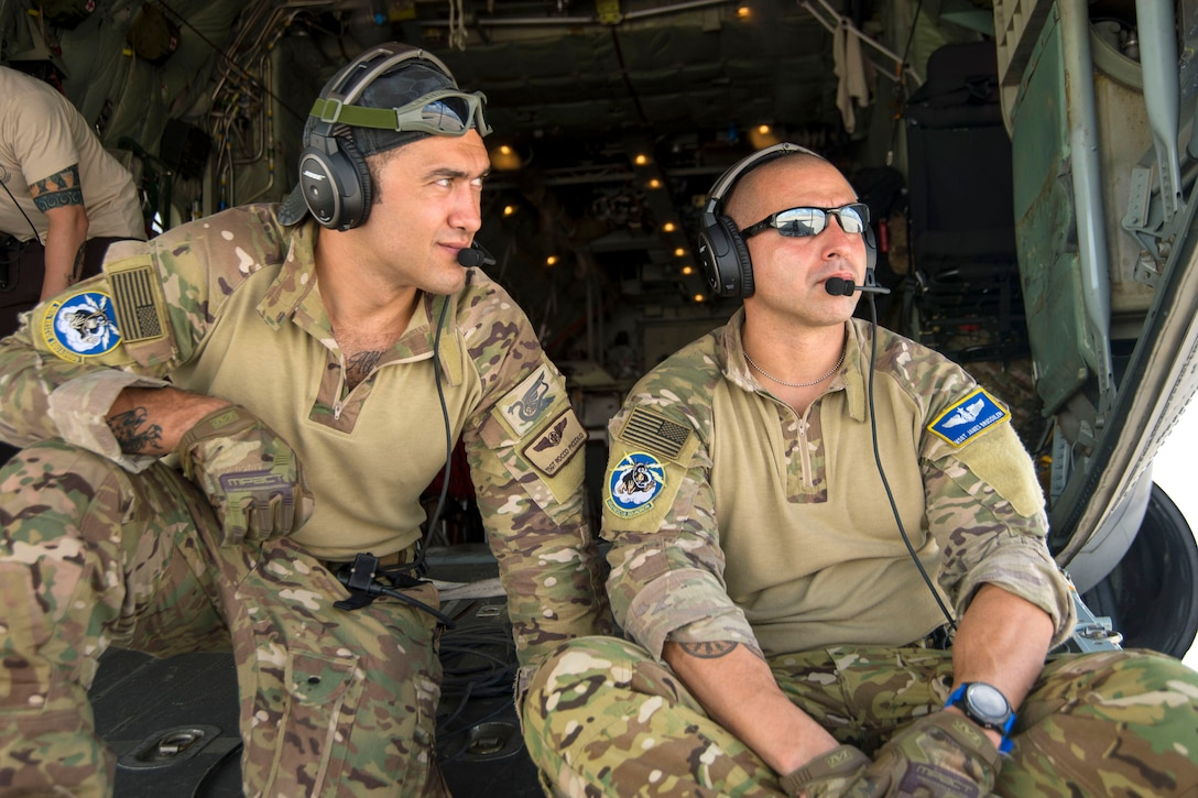 Two airmen sit on the back of an airplane.