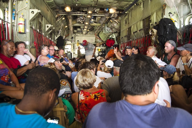 Evacuees sit on the floor of an aircraft.