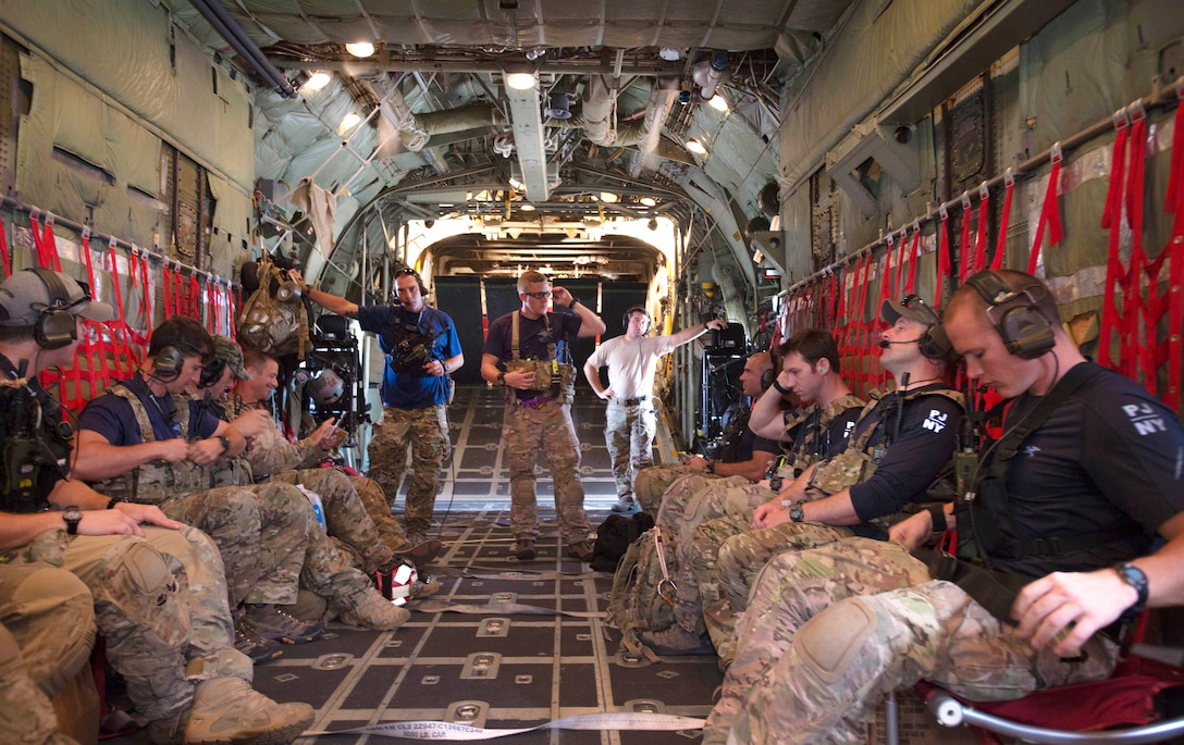 A group of airmen sit in an airplane..