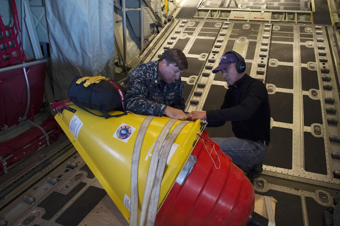 Navy Lt. Cmdr. John Woods, from the Office of Naval Research, reserve component, and Ignatius Rigor from the University of Washington prepare an Air-Deployable Expendable Ice Buoy for deployment in the high Arctic Ocean near the North Pole.