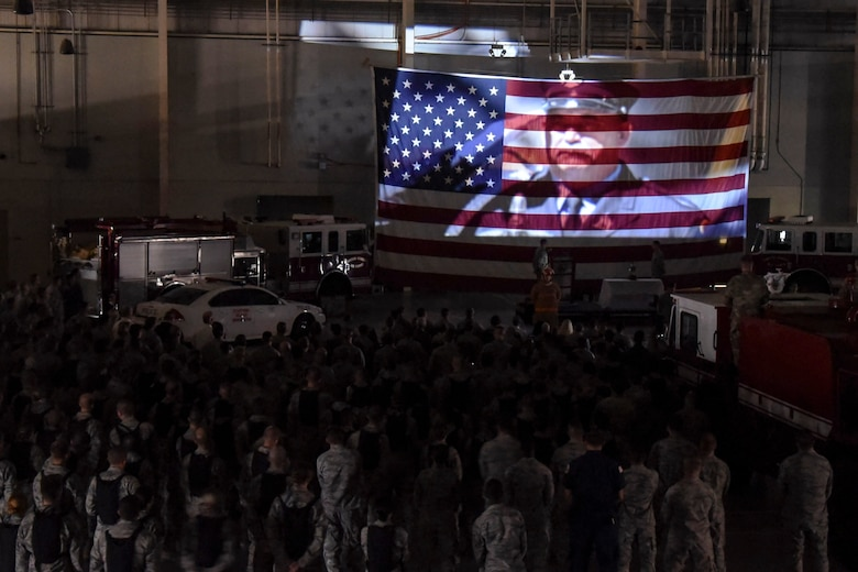 Attendees of the 9/11 Memorial watch a tribute video projected onto a flag at the  Louis F. Garland Department of Defense Fire Academy high bay on Goodfellow Air Force Base, Texas, Sept. 11, 2017. The video showed footage of the towers falling and paid tribute to all the first responders who died on 9/11. (U.S. Air Force photo by Airman Zachary Chapman/Released)