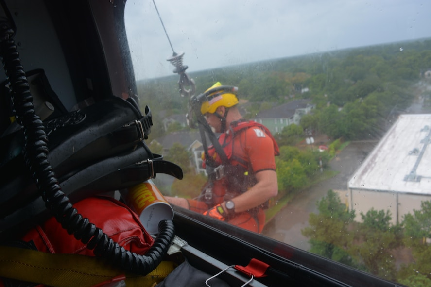 Petty Officer 2nd Class Graham McGinnis, an aviation survival technician, responds to a rescue request in Houston, Aug. 27, 2017. The Coast Guard partners with local Emergency Operations Centers and established an Incident Command Post to manage search and rescue operations. U.S. Coast Guard courtesy photo by Petty Officer 2nd Class Bob Hovey