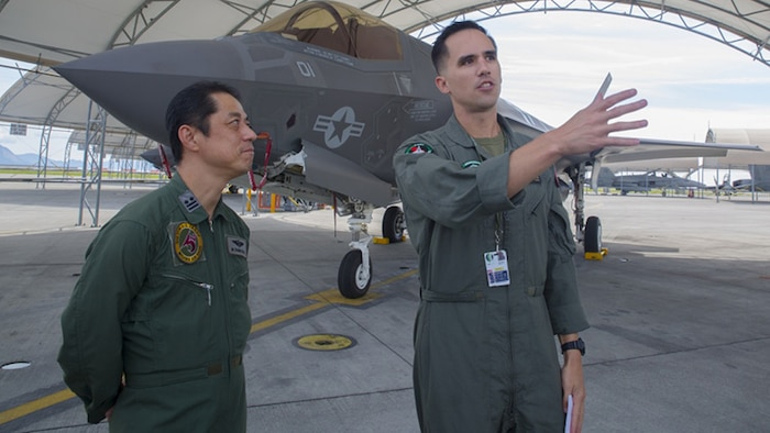 U.S. Marine Corps Maj. Adam Wellington, right, aircraft maintenance officer for Marine Fighter Attack Squadron 121, answers questions for Japan Air Self-Defense Force Lt. Col. Mamoru Yamaura, F-35A Lightning II program office chief with Third Air Wing, during an educational tour and class centered on the F-35B Lightning II at Marine Corps Air Station Iwakuni, Japan, Sept. 13, 2017.