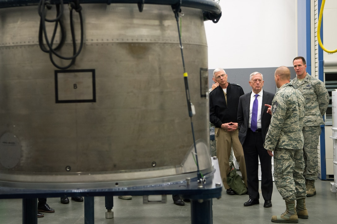 Defense Secretary Jim Mattis and several service members stand next to equipment at a missile facility.