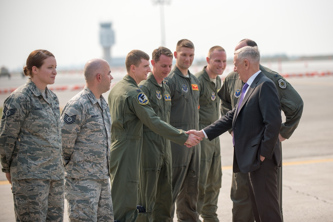 Defense Secretary Jim Mattis shakes hands with airmen.