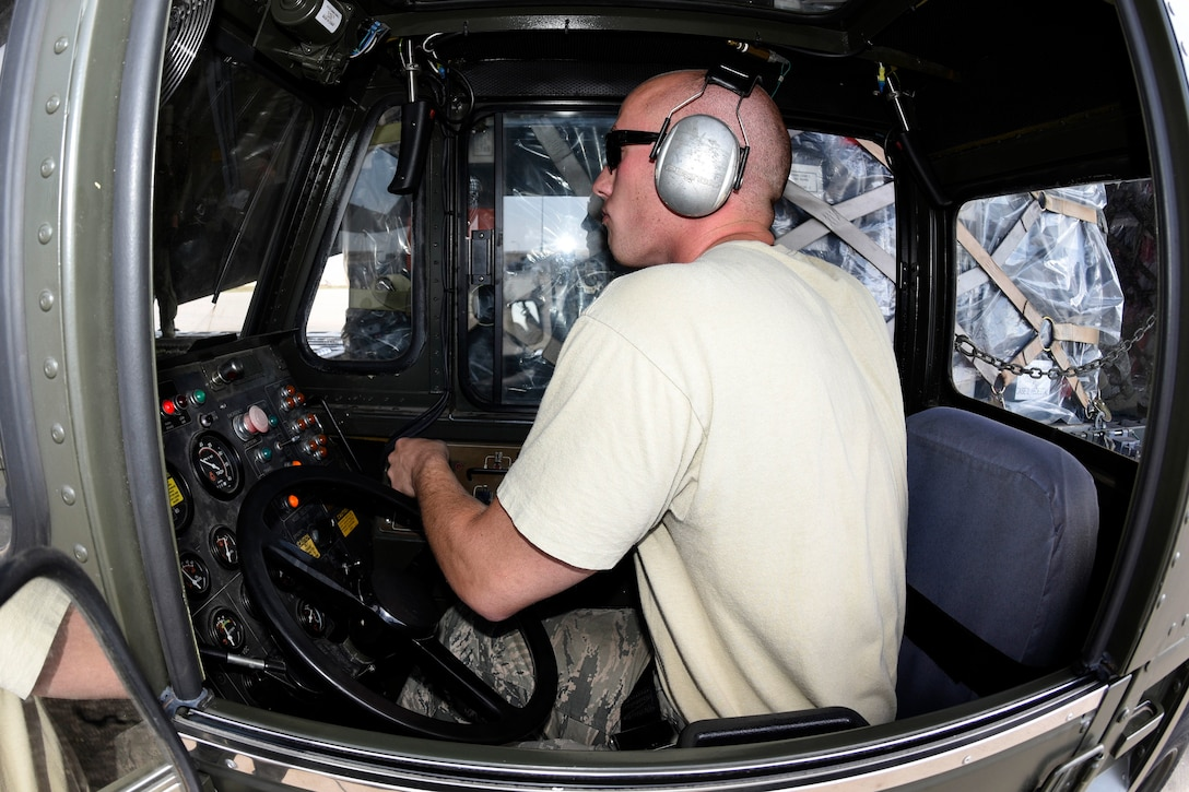 An airman controls the movement of uploading equipment and palletized cargo onto a C-17A Globemaster III.