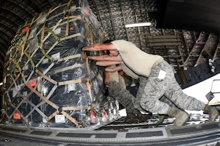 Airmen push palletized cargo onto a C-17A Globemaster III