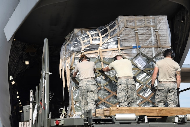 Airmen push palletized cargo onto a C-17A Globemaster III