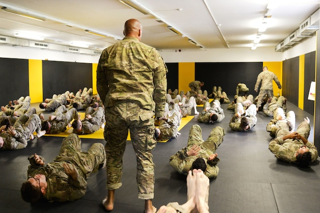 Soldiers conduct warm up exercises before participating in a basic combatives course