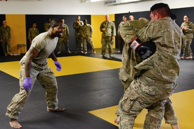 Staff Sgt. Robert Ward, left, observes his students conducting punching drills during a basic combatives course