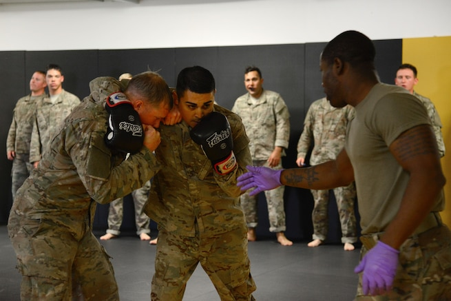 Staff Sgt. Robert Ward, right, prepares his students to conduct punching drills during a basic combatives course.