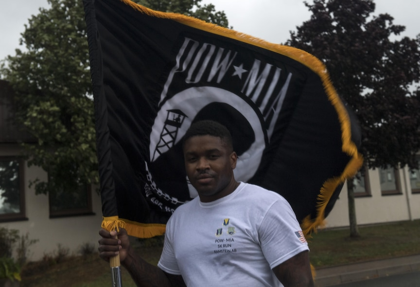 U.S. Air Force Staff Sgt. Courtland Little, 435th Security Forces Squadron resource advisor, holds the POW/MIA guidon for the Tri-Wing POW/MIA Memorial Run on Ramstein Air Base, Germany, Sept. 13, 2017. Little coordinated this year's memorial run, garnering approximately 1,200 participants for the run in honor of prisoners of war and missing in action service members. (U.S. Air Force photo by Senior Airman Tryphena Mayhugh)