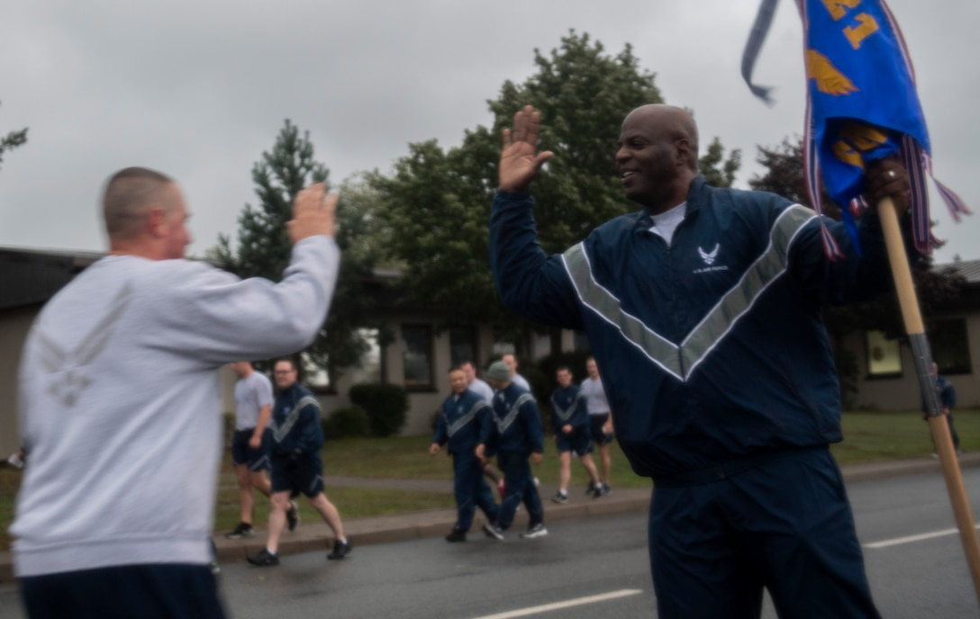 U.S. Air Force Chief Master Sgt. David E. Satchell, 521st Air Mobility Operations Wing command chief, high-fives a participant in the Tri-Wing POW/MIA Memorial Run as he runs to the finish line on Ramstein Air Base, Germany, Sept. 13, 2017. The run was held in honor of National Prisoners of War/Missing in Action Day, which is observed every year on the third Friday in September. (U.S. Air Force photo by Senior Airman Tryphena Mayhugh)