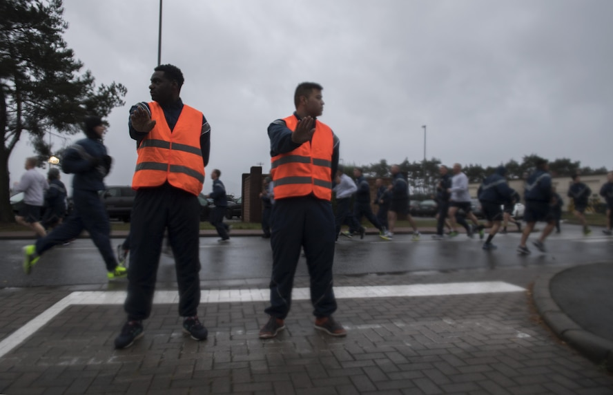 U.S. Air Force Senior Airman Brandon Smith (left) and Airman 1st Class Mark Ames, both 86th Logistic Readiness Squadron traffic management office apprentices, prevent traffic from entering the road during the Tri-Wing POW/MIA Memorial Run on Ramstein Air Base, Germany, Sept. 13, 2017. Approximately 1,200 Airmen assigned to the 86th Airlift Wing, 521st Air Mobility Operations Wing, and 435th Air Ground Operations Wing participated in the run honoring those who were or are prisoners of war or missing in action. (U.S. Air Force photo by Senior Airman Tryphena Mayhugh)