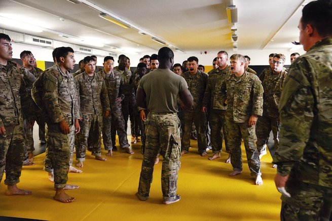 Staff Sgt. Robert Ward, middle, briefs his students before they conduct punching drills during a basic combatives course