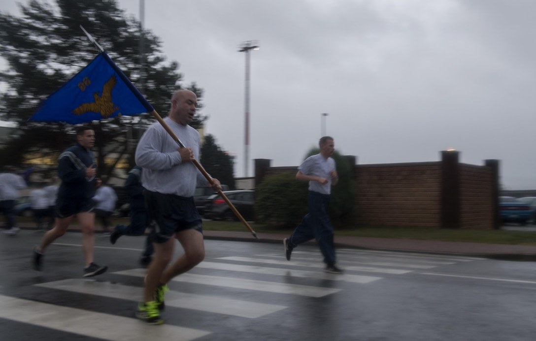 U.S. Air Force Chief Master Sgt. Aaron D. Bennett, 86th Airlift Wing command chief, runs while carrying the 86th AW's guidon during the Tri-Wing POW/MIA Memorial Run on Ramstein Air Base, Germany, Sept. 13, 2017. The run was held to honor prisoners of war and missing in action service members and was attended by Airmen assigned to the 86th AW, 521st Air Mobility Operations Wing, and 435th Air Ground Operations Wing. (U.S. Air Force photo by Senior Airman Tryphena Mayhugh)