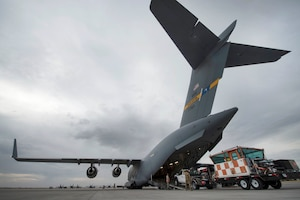 Airmen load a mobile traffic control tower system onto a C-17 Globemaster III
