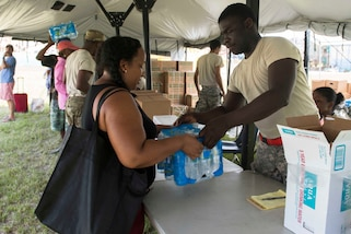 Residents receive food and water from Virgin Islands Army National Guardsmen in St. John, Virgin Islands