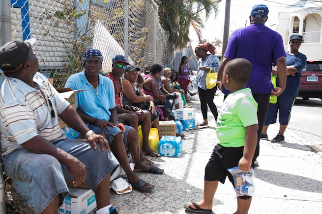 Virgin Islanders talk after receiving water and food distributed by Virgin Islands Army National Guardsmen