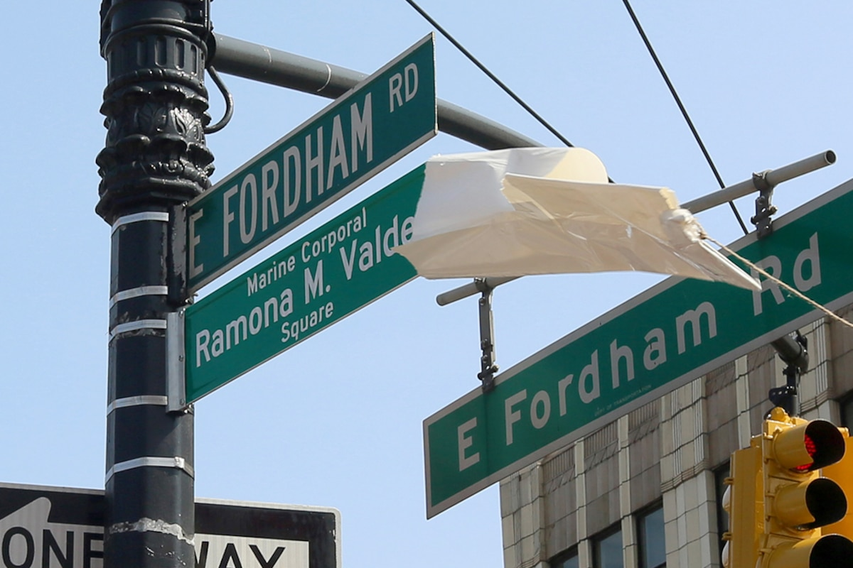 A white sheet is pulled off a street sign.