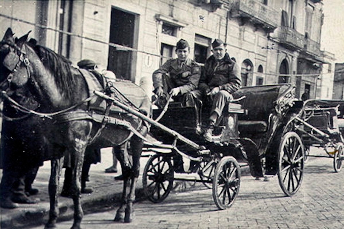 Two service members sit in a carriage pulled by a horse.