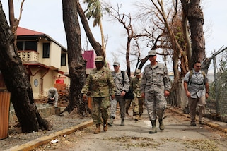 A group of service members and civilians walk down a road with damage to trees and structures.