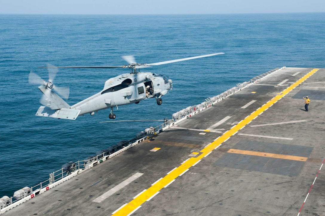 """170913-N-ZS023-020 U.S. 5TH FLEET AREA OF OPERATIONS (Sept. 13, 2017) An MH-60S Sea Hawk assigned to the """"Wildcards"""" of Helicopter Sea Combat Squadron (HSC) 23 lands on the flight deck of the amphibious assault ship USS America (LHA 6) after conducting flight operations in support of Alligator Dagger 2017 Alligator Dagger is a dedicated, unilateral combat rehearsal led by Naval Amphibious Force, Task Force 51/5th Marine Expeditionary Brigade, in which combined Navy and Marine Corps units of the America Amphibious Ready Group and embarked 15th Marine Expeditionary Unit are to practice, rehearse and exercise integrated capabilities that are available to U.S. Central Command both afloat and ashore. (U.S. Navy photo by Mass Communication Specialist Seaman Vance Hand/Released)"""