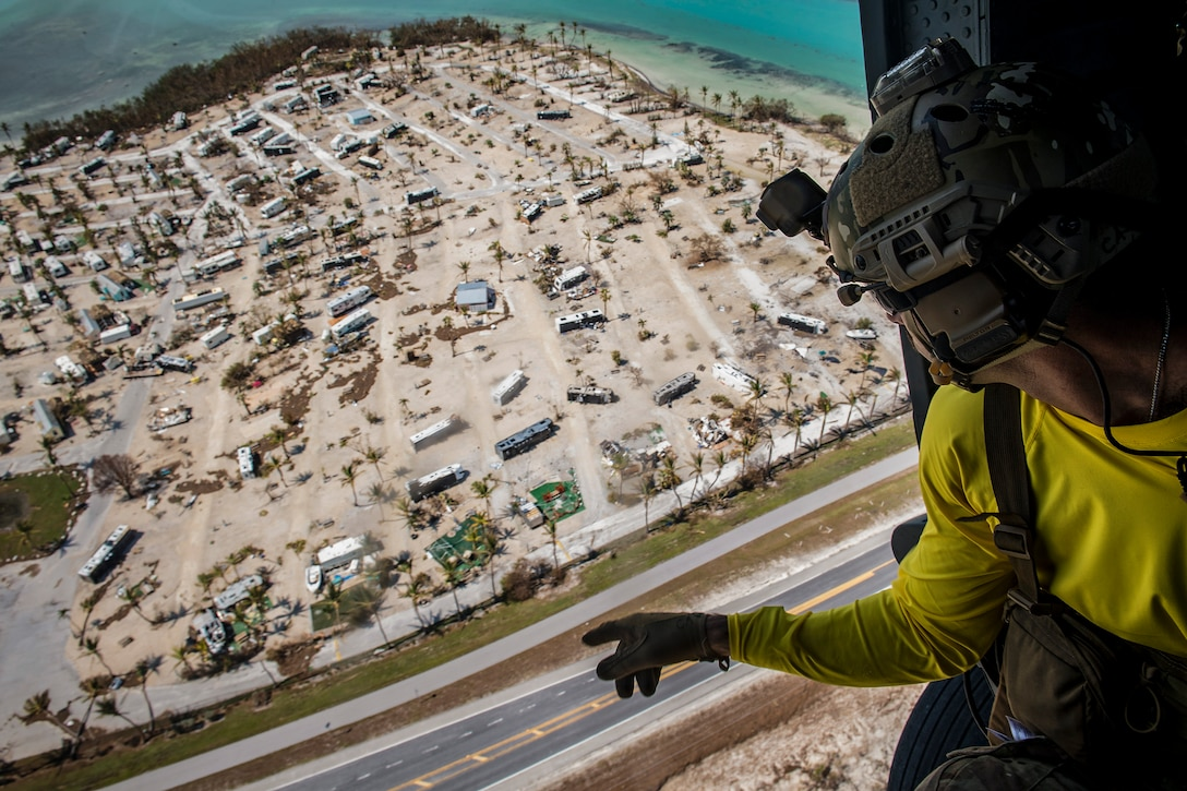 An airman aboard a helicopter points while looking over a damaged beachfront trailer park.