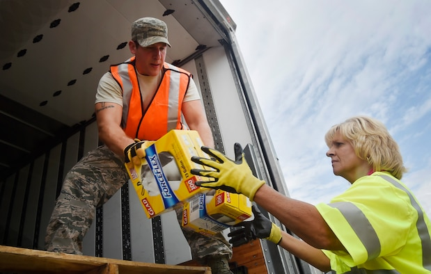 Staff Sgt. Micah Hallman, left, 43rd Air Mobility Squadron air transportation specialist, Pope Army Airfield, N.C., hands boxes to Jodi Johnson, right, U.S. Department of Homeland Security - Federal Emergency Management Agency (FEMA), as they download goods and commodities in support of Hurricane Irma relief efforts at Joint Base Charleston's North Auxiliary Airfield, S.C., Sept. 13, 2017. The airfield acts as a receiving and distribution staging area for goods and commodities to be transported to hurricane victims here and areas of the southeast over the next few weeks. Airmen of the 43rd Air Mobility Operations Group and FEMA are working side-by-side executing relief efforts. (U.S. Air Force photo by Staff Sgt. Christopher Hubenthal)