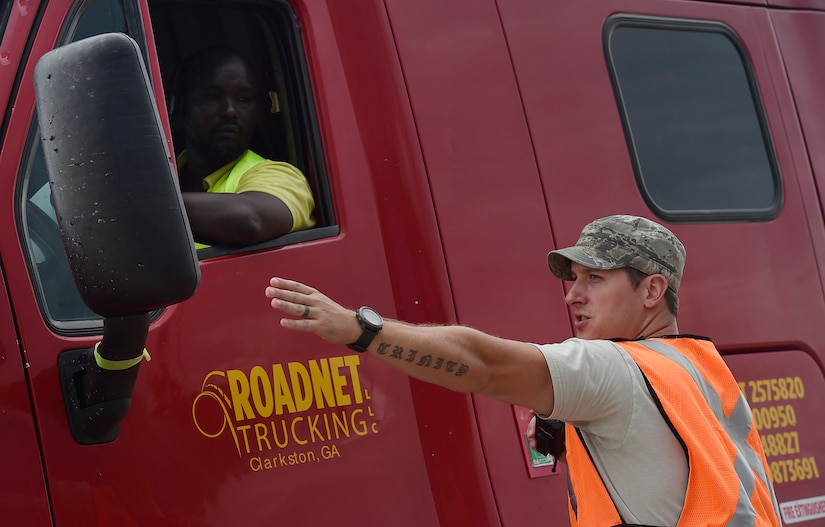 Staff Sgt. Micah Hallman, 43rd Air Mobility Squadron air transportation specialist, Pope Army Airfield, N.C., directs a truck driver transporting goods prepped to support Hurricane Irma relief efforts at Joint Base Charleston's North Auxiliary Airfield, S.C., Sept. 13, 2017. The airfield acts as a receiving and distribution staging area for goods and commodities being transported to hurricane victims here and areas to the southeast over the next few weeks. Airmen of the 43rd Air Mobility Operations Group and U.S. Department of Homeland Security - Federal Emergency Management Agency (FEMA), are working side-by-side executing relief efforts. (U.S. Air Force photo by Staff Sgt. Christopher Hubenthal)
