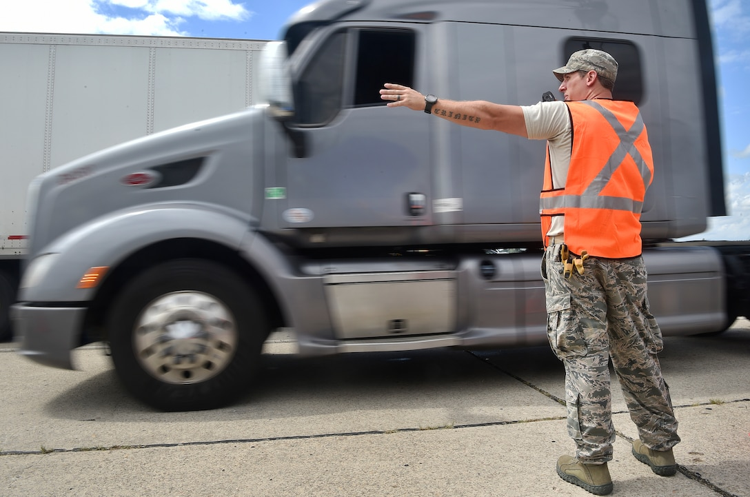 Staff Sgt. Micah Hallman, 43rd Air Mobility Squadron air transportation specialist, Pope Army Airfield, N.C., directs the movement of trucks transporting goods prepped to support Hurricane Irma relief efforts at Joint Base Charleston's North Auxiliary Airfield, S.C., Sept. 13, 2017. The airfield acts as a receiving and distribution staging area for goods and commodities being transported to hurricane victims here and areas to the southeast over the next few weeks. Airmen of the 43rd Air Mobility Operations Group and U.S. Department of Homeland Security - Federal Emergency Management Agency (FEMA), are working side-by-side executing relief efforts. (U.S. Air Force photo by Staff Sgt. Christopher Hubenthal)