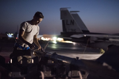Air Force Airman 1st Class Pedro Curiel-Lamas, 332nd Expeditionary Maintenance Squadron weapons load crew member, prepares a missile