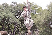 Cpl. Kristen Gray, finance clerk, 9th Financial Management Services Unit, Special Troops Battalion, 1st Infantry Division Sustainment Brigade, climbs a rope May 11 during an optical challenge for a qualifying Army Warrior competition. Gray is one of 10 Army-wide personnel who qualified to compete at the Army Best Warrior Competition.