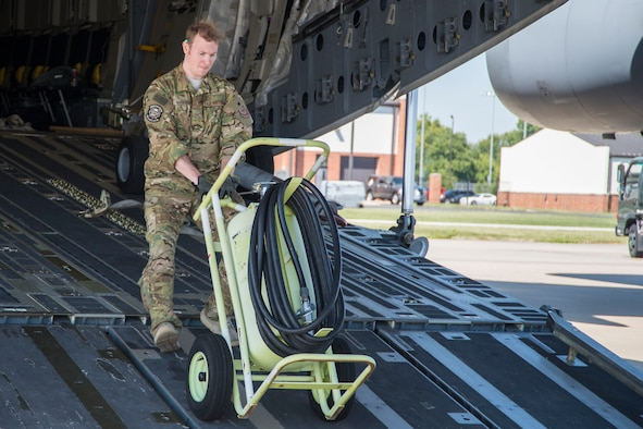 A member from Joint Base Charleston, S.C. unloads equipment from a C-17 Globemaster III in preparation for Hurricane Irma, at Scott Air Force Base, Ill
