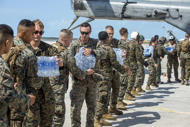 Marines stand in a line passing bottles of water out of an aircraft.