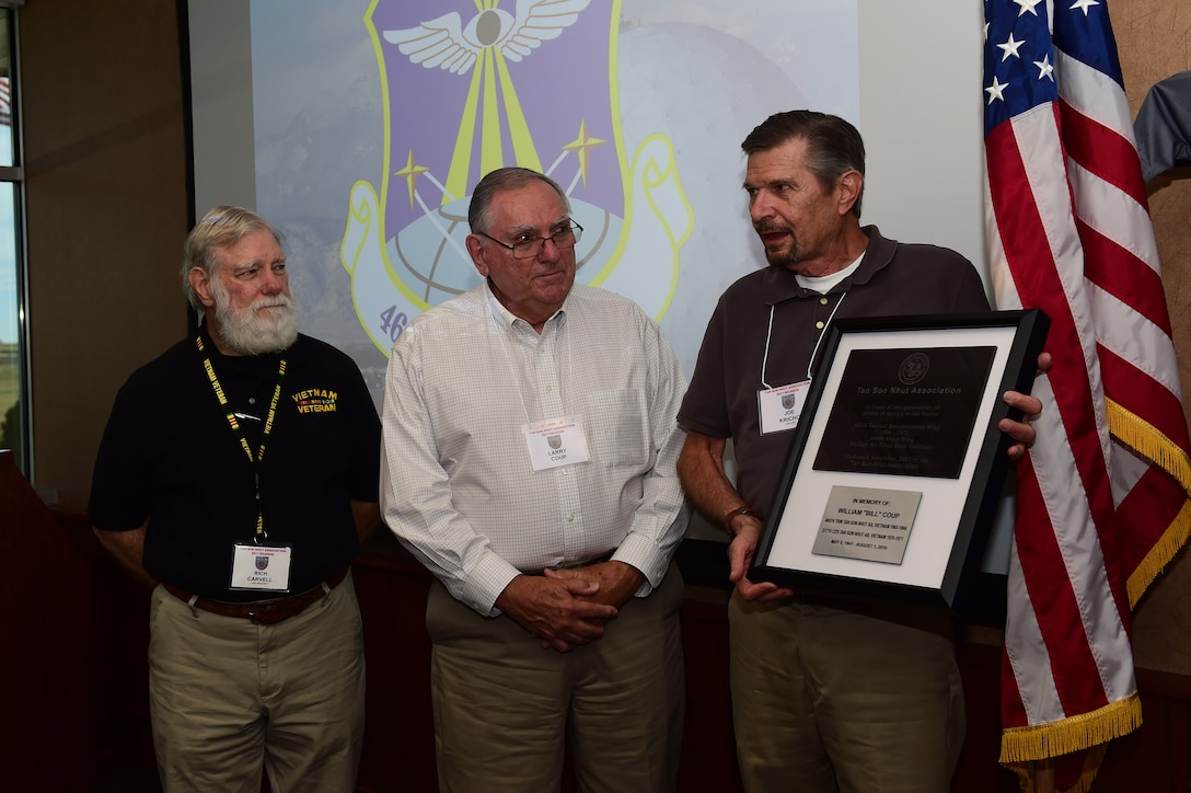 Joe Kricho, Tan Son Nhut Association director, Larry Coup, Tan Son Nhut Association member, and Richard Carvell, Tan Son Nhut Association vice president, present a plaque Sept. 14, 2017, in the 460th Headquarters building on Buckley Air Force Base, Colo.