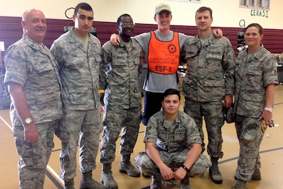A row of airmen and a civilian pose for a photo.
