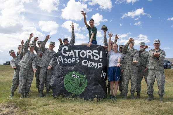 "Reserve Citizen Airmen from the 19th Space Operations Squadron do the ""Gator Chomp"" while posing with the newly painted Spirit Rock on Thursday, Sep. 14, 2017."