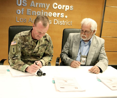 Col. Kirk Gibbs, commander of the U.S. Army Corps of Engineers Los Angeles District, left, signs the labor-management agreement between the District and its Union, as Vern Bernhardt, president of the National Federation of Federal Employees Union Local Chapter No. 777, looks on during a Sept. 12 signing ceremony at the District's office in downtown LA.