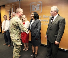 Col. Kirk Gibbs, commander of the U.S. Army Corps of Engineers Los Angeles District, center left, congratulates LaShawn Richardson, realty specialist and contracting officer representative with the District's Asset Management Division, second from right, for her hard work as a member of the negotiating team during a Sept. 12 labor-management agreement signing ceremony at the District's office in downtown LA. Gibbs presented District coins to all members of the team who spent about 18 hours a week during the past five months working on the agreement.