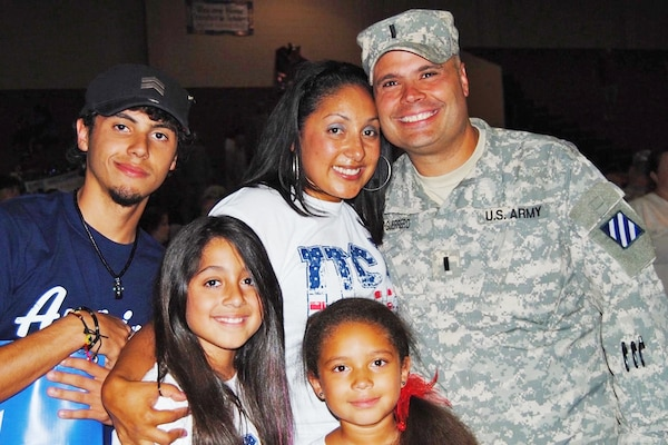 A soldier is pictured with his family.