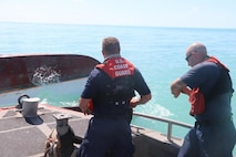 A 35-foot long range interceptor crewmember writes down an overturned vessel's registration number found off the coast of Key West, Florida, Sept. 13, 2017. Coast Guard Cutter Hamilton's crew was deployed to Florida in support of Hurricane Irma relief operations. U.S. Coast Guard photo by Ensign Samantha Corcoran.