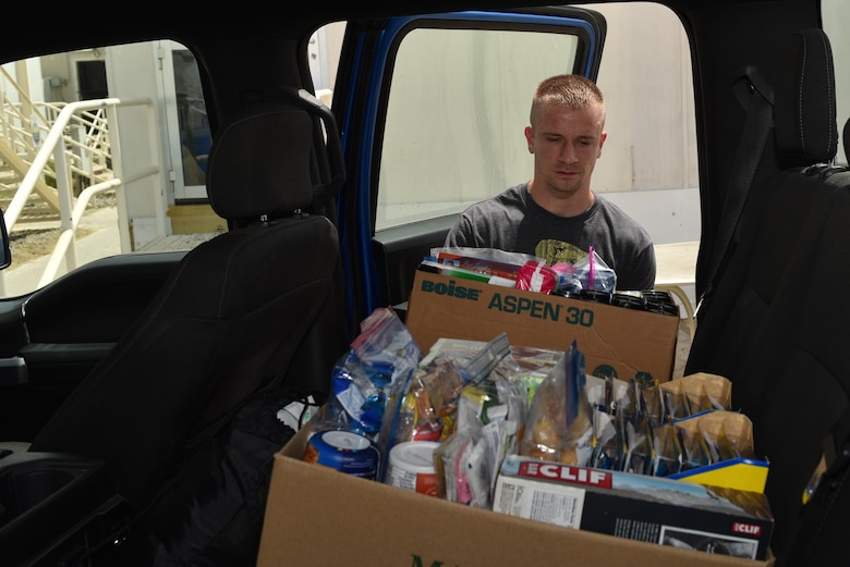 Tech. Sgt. Adam Martin, vehicle maintenance technician with the 380th Expeditionary Logistics Readiness Squadron, loads boxes of donated goods into a truck at Al Dhafra Air Base, United Arab Emirates, Sept. 8, 2017.