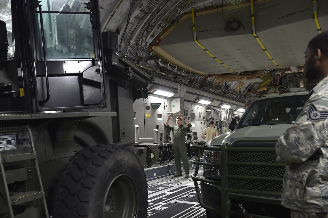 Staff Sgt. Dungan Farver, 16th Airlift Squadron loadmaster, signals a 10K All Terrain forklift onto a C-17 Globemaster III aircraft, Sep. 13, 2017, at Scott Air Force Base, Ill.   A 17-member contingency response team from the 821st Contingency Response Group from Travis Air Force Base, Calif., deployed to Homestead Air Reserve Base, Fla., to augment the 439th Airlift Wing airfield capabilities in support of Hurricane Irma relief efforts.  (U.S. Air Force photo by Tech. Sgt. Liliana Moreno/Released)