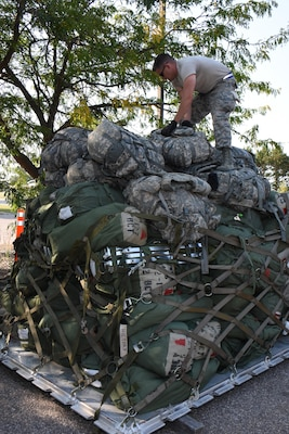 Wisconsin Air National Guard member is palletizing luggage for a flight to Florida.