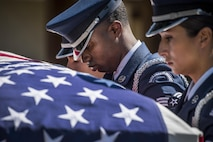 Senior Airman Antonio Samuels, 453rd Electronic Warfare Squadron, bows his head as he and fellow Airmen carry a casket out of a hearse during an honor guard graduation ceremony at Eglin Air Force Base, Fla., Sept. 8, 2017. The graduation performance included flag detail, rifle volley, pall bearers and bugle demonstrations. (U.S. Air Force photo by Samuel King Jr.)
